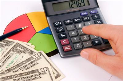 Finger pressing on a calculator to calculate the finnancial report